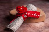 Cardboard heart and a roll of fabric tied with ribbon.Valentine's day. — Stock Photo