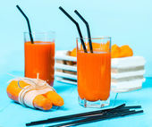 Freshly squeezed carrot juice in the glasses.A box with purified carrot on a blue wooden background. — Stock Photo