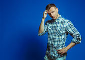Fasion portrait of young handsome man in shirt and jeans over bl — Stock Photo