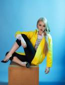 Portrait of blond model in fashion yellow coat sitting over blue — Stock Photo