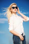 Beautiful young woman in white shirt, jeans ad trendy sunglasses — Stock Photo
