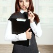 Secretary holds a black folder on your chest and held a pen to h — Stock Photo #64549339