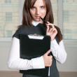 Girl holds a folder and puts a hand with pen to her mouth — Stock Photo #64551601