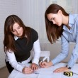Two female architects studying blueprints areas — Stock Photo #64554481