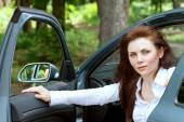 Girl opens the door exiting the car — Stock Photo