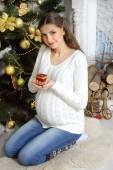Pregnant girl sits on his lap and holding a candle — Stock Photo