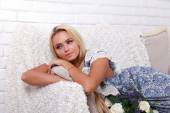 Blond girl in blue sundress lying on the couch — Stock Photo