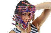 Girl covers her face with her hands painted in colorful paint — Stock fotografie