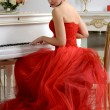 Woman in a red dress playing on a piano — Stock Photo #70421297