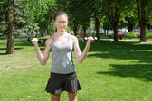 Activities girl doing exercise with light dumbbells  — Stock fotografie