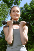 Sports woman doing exercises with lightweight dumbbells  — Foto Stock