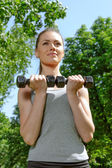 Sports girl doing exercise with lightweight dumbbells — Foto Stock