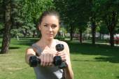 Fitness woman mimics a hit with light dumbbells — Stock Photo