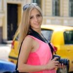 Girl tourist walks around town with a camera — Stock Photo #77735476