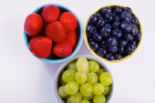 Blueberries, strawberries and grapes in cans — Stock Photo