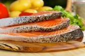 Delicious  portion of fresh salmon fillet with vegetables on background — Stock Photo
