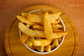Potatoes fries in a white paper bag on wooden board — Stock Photo