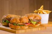 Tasty burger with melted cheese and thick succulent ground chicken patty, lettuce, tomato, onion, sesame bun standing on wooden table — Foto de Stock