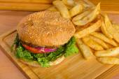 Tasty burger with melted cheese and thick succulent ground beef patty, lettuce, tomato, onion, sesame bun standing on wooden table — Foto de Stock