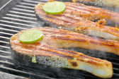 Fresh salmon fillet with lime cooked on a grill — Stock Photo