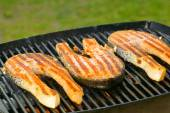 Portion of fresh salmon fillet on a grill — Stock Photo