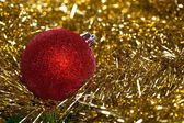 Red christmas ball with yellow tinsel — Stock Photo