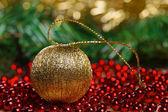 Yellow christmas ball on red beads — Stock Photo