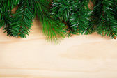 Green fir-tree branches on wooden background — Stock Photo