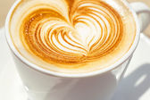 Cappuchino or latte coffe in a white cup with heart shaped foam — Stock Photo