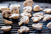 Champignon mushrooms on grill — Stock Photo