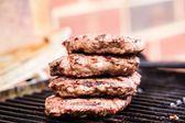Pile of grilled ground beef patties on BBQ — Stock Photo
