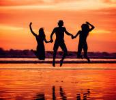 Silhouettes of happy young friends jumping on the beach  against red sunset — Stock Photo