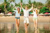 Group of happy young people walking along the beach on beautiful summer sunset — Stock Photo