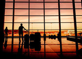 Silhouette of airline passengers in an airport lounge at the wide observation window against a surreal sunset — Stock Photo