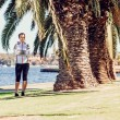 Healthy lifestyle young sporty woman having break between palm trees after jogging at tropical park — Stock Photo #78241856