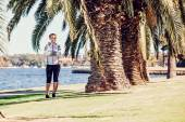 Healthy lifestyle young sporty woman having break between palm trees after jogging at tropical park — Stock Photo