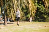 Healthy lifestyle young sporty woman jogging at tropical park along palm trees — Stock Photo