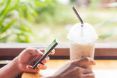 Hand hold coffee and use smart phone — Stok fotoğraf