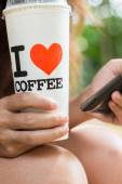 Women hold ice coffee and use smart phone mobile — Stockfoto