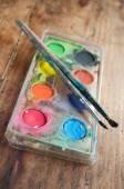 Watercolor palette witth pencilscloseup on wooden background — ストック写真