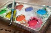 Watercolor palette witth pencilscloseup on wooden background — Stock Photo