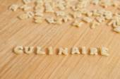 "Alphabet pasta forming the text ""culinaire"" (culinary in french) on wooden background — Stock Photo"