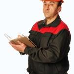 Worker in a orange helmet writes in a notebook — Stock Photo #60717455