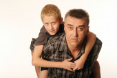 Ten year old son cheerfully embraced his father sitting on his back — Stock Photo