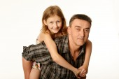 Twelve year old daughter hugging her father sitting on his back — Stock Photo