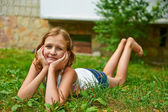 Twelve year old girl lies on the grass and smiling — Stock Photo