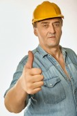 Worker in a yellow hardhat showing gesture approval — Stock Photo