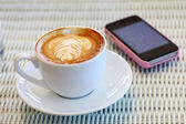 Coffee and mobile phone on white table in cafe — Stock Photo