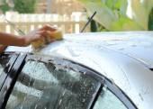 Woman hand hold sponge washing car — Stock Photo