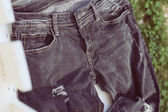 Black jeans on white wood, retro tone image — Stock Photo